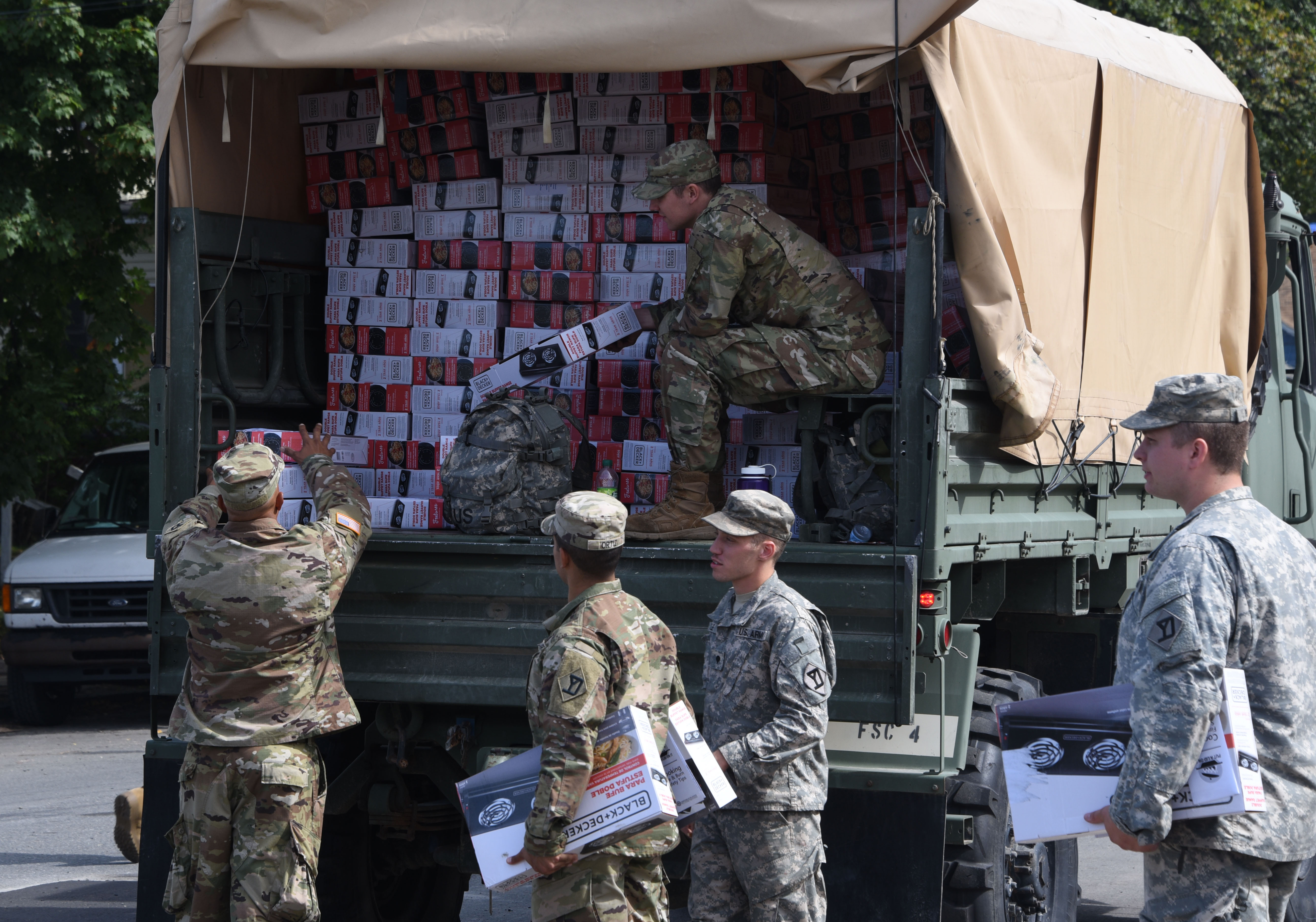 Soldiers of the 101 FSC, 101st  Engineering Battalion, hand out boxes of hot plates in Lawrence, Massachusetts on Sept. 23, 2018. National Guard soldiers and airmen delivered hundreds of hotplates to families throughout Lawrence after the gas explosions in the Merrimack Valley.